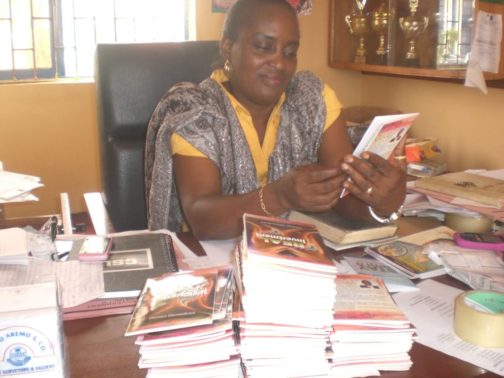 Mrs Lufadeju Recieving 160 Copies of Real Investment for her school